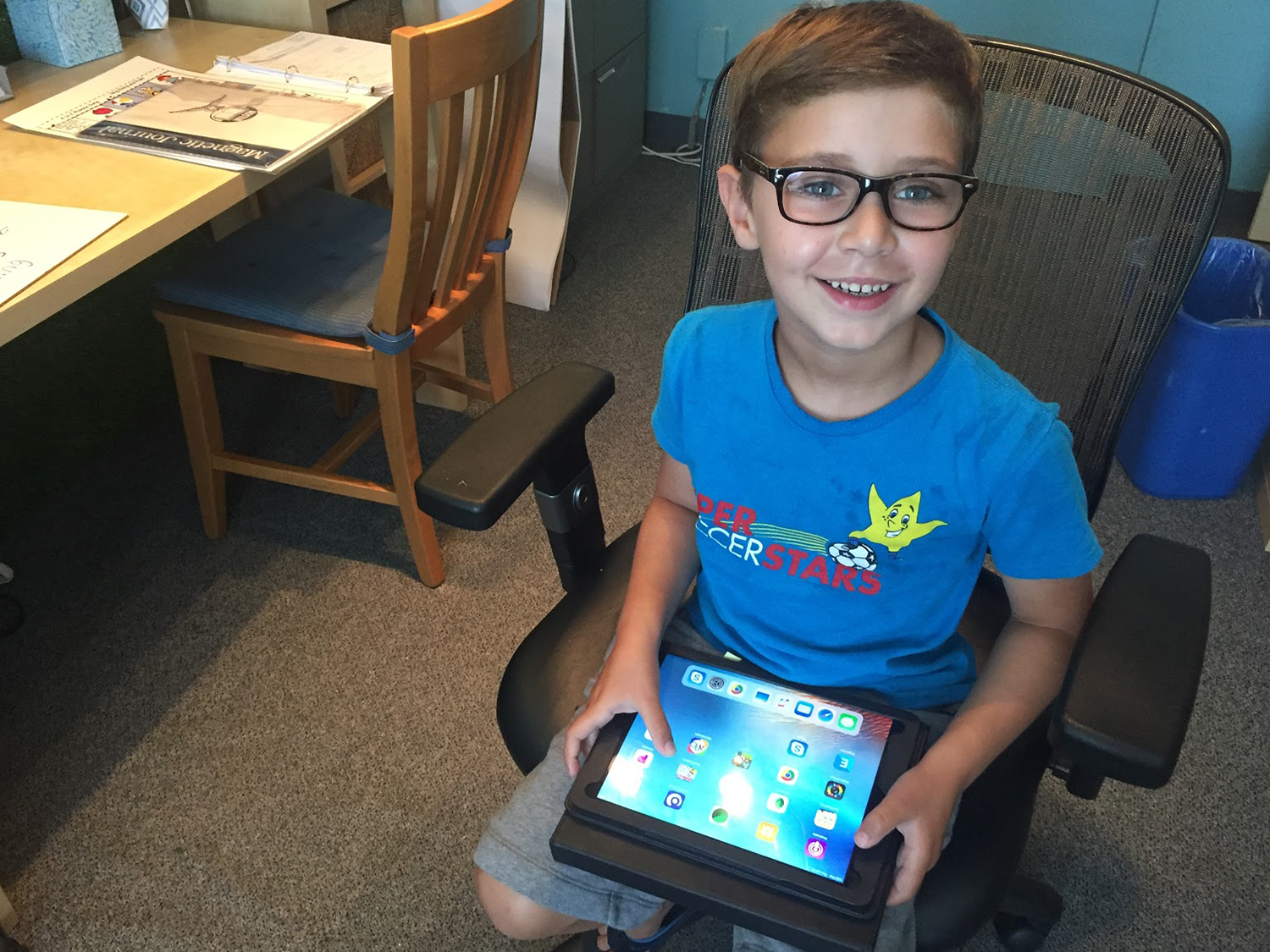 Educational Technology Tools, young boy wearing glasses sitting in a chair holding an tablet