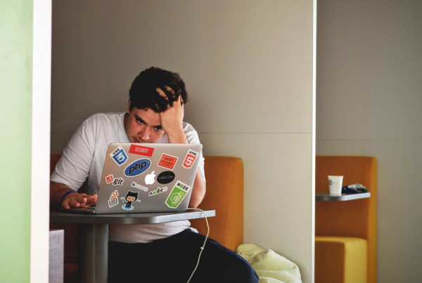 Career Interest Coaching, Picture of a young kid on a laptop holding his head in frustration at a desk