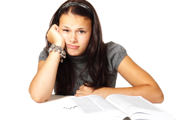 Do Middle School Grades Really Matter? Hint: They Do!, image of girl in front of a book making an overwhelmed face.