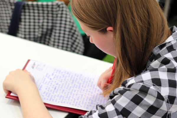 Homework Difficulties: Advice for Parents with Struggling Students, image of a girl doing homework at a desk with a notepad and pen.