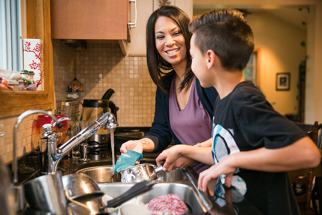 What Does Life Look Like for Social Distancing With School-Age Kids, image of a mother and son doing dishes together at home