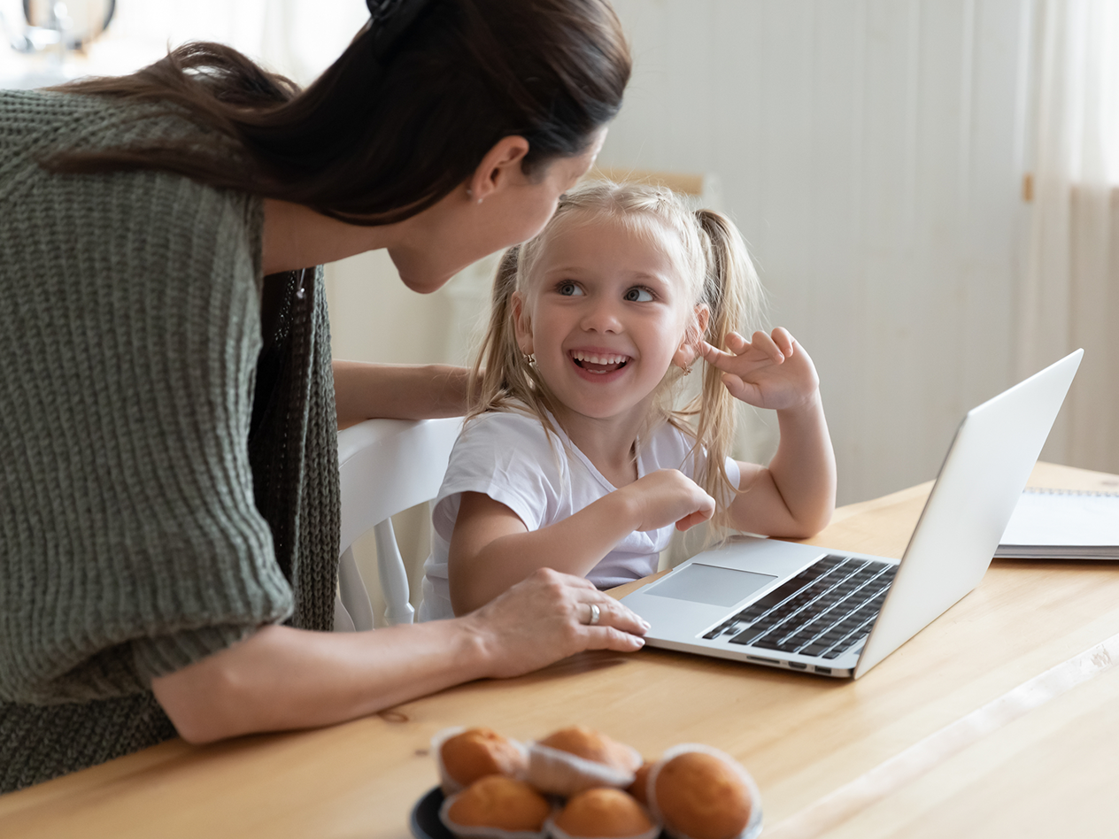 Home Learning Resources, image of a mother and daughter at home next to a laptop smiling