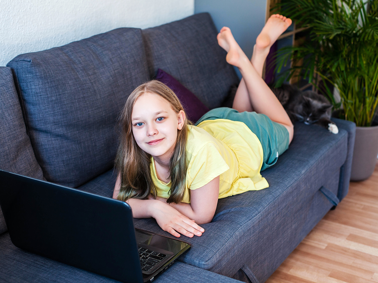 how to prevent summer learning loss, image of young girl on couch with laptop