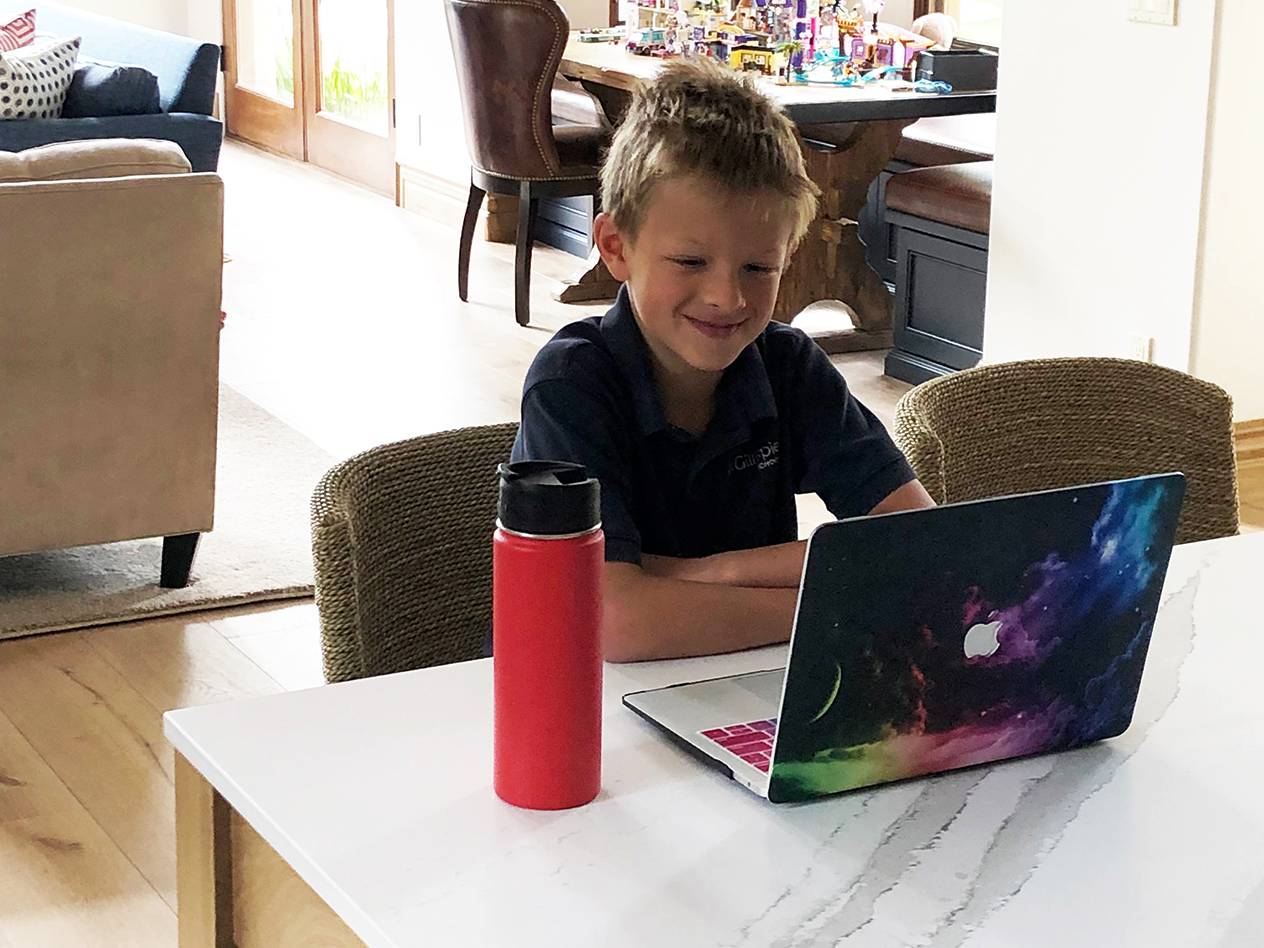 Distance Learning During Covid-19, image of a kid smiling with a laptop and a water bottle at his desk