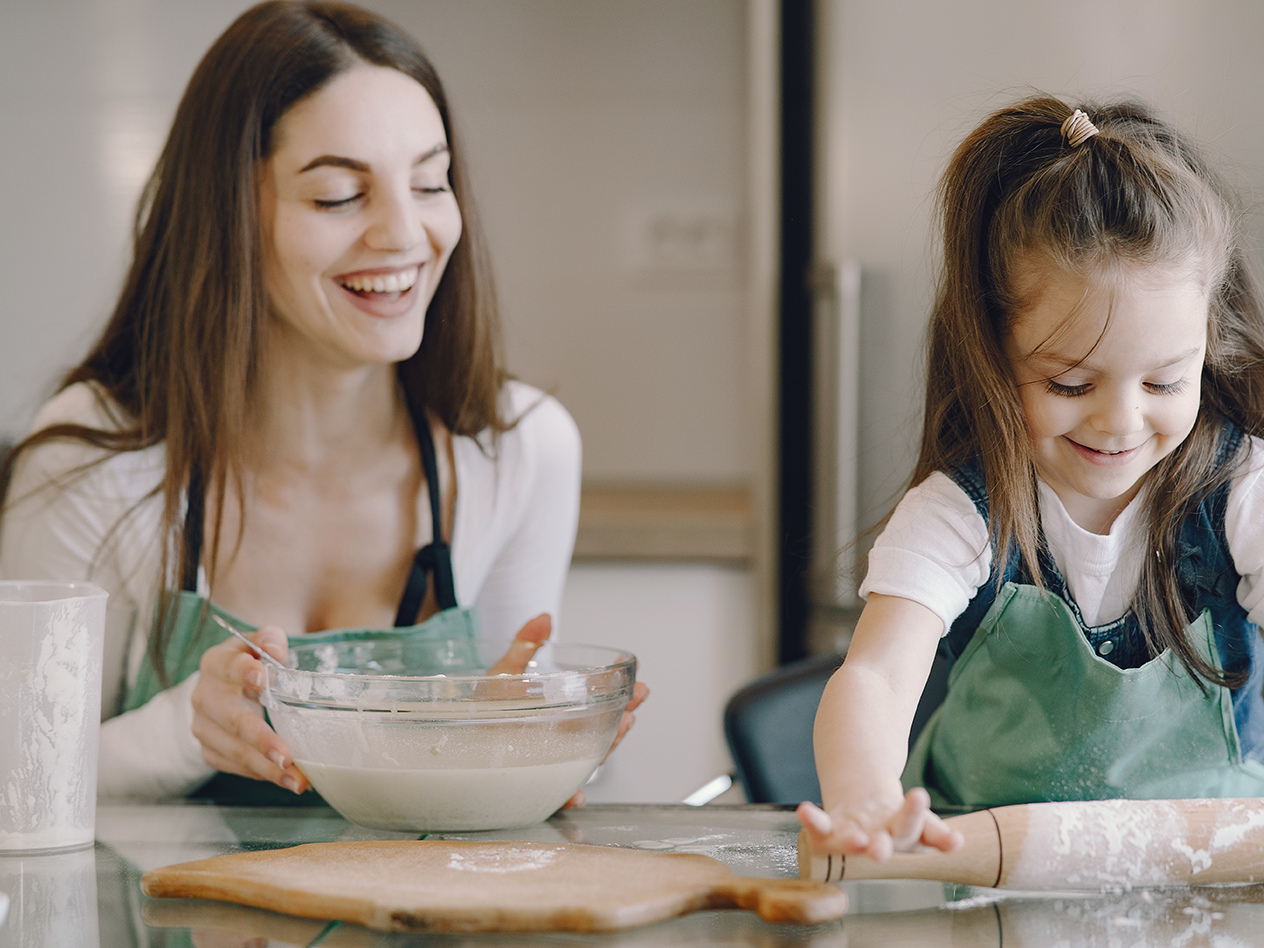 Summer Activities for Kids with ADHD, image of mom and daughter cooking in the kitchen with dough