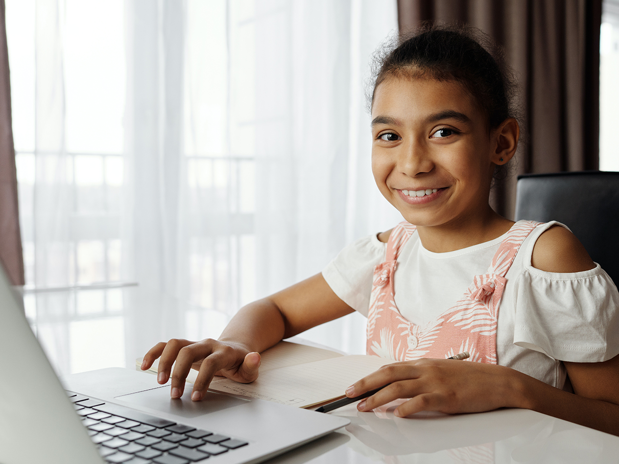 12 Ways to Stay Healthy for Online Students, image of a young girl at the computer smiling to the camera