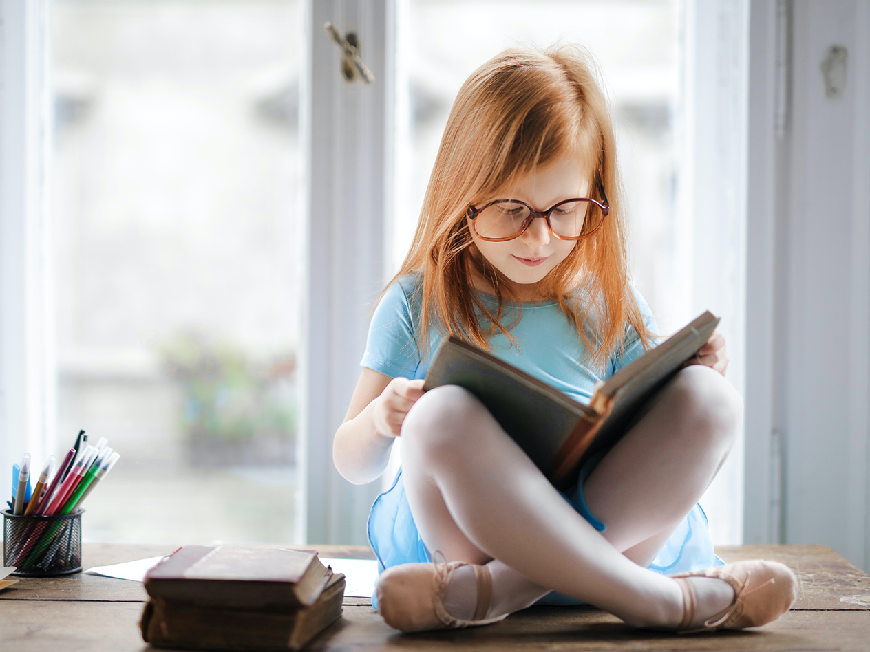 identify dyslexia, What Parents Need to Know About Dyslexia and How It Is Assessed in Today's Schools, image of a young girl sitting crossed legged reading a book