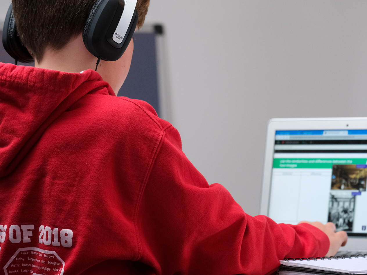 The Effects of COVID-19 on Student Learning, image of a kid with headphones working on classwork for school on a laptop